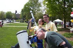 Blair advertises for a campus sponsor while a member of the public takes a look through Jacob's telescope.